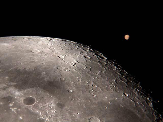 Sur cette image prise depuis la Terre par Wayman, Mars apparaît bien petite dans l'objectif du télescope. La présence de la Lune permet de se rendre compte de la difficulté de l'observation des surfaces planétaires à cette distance.